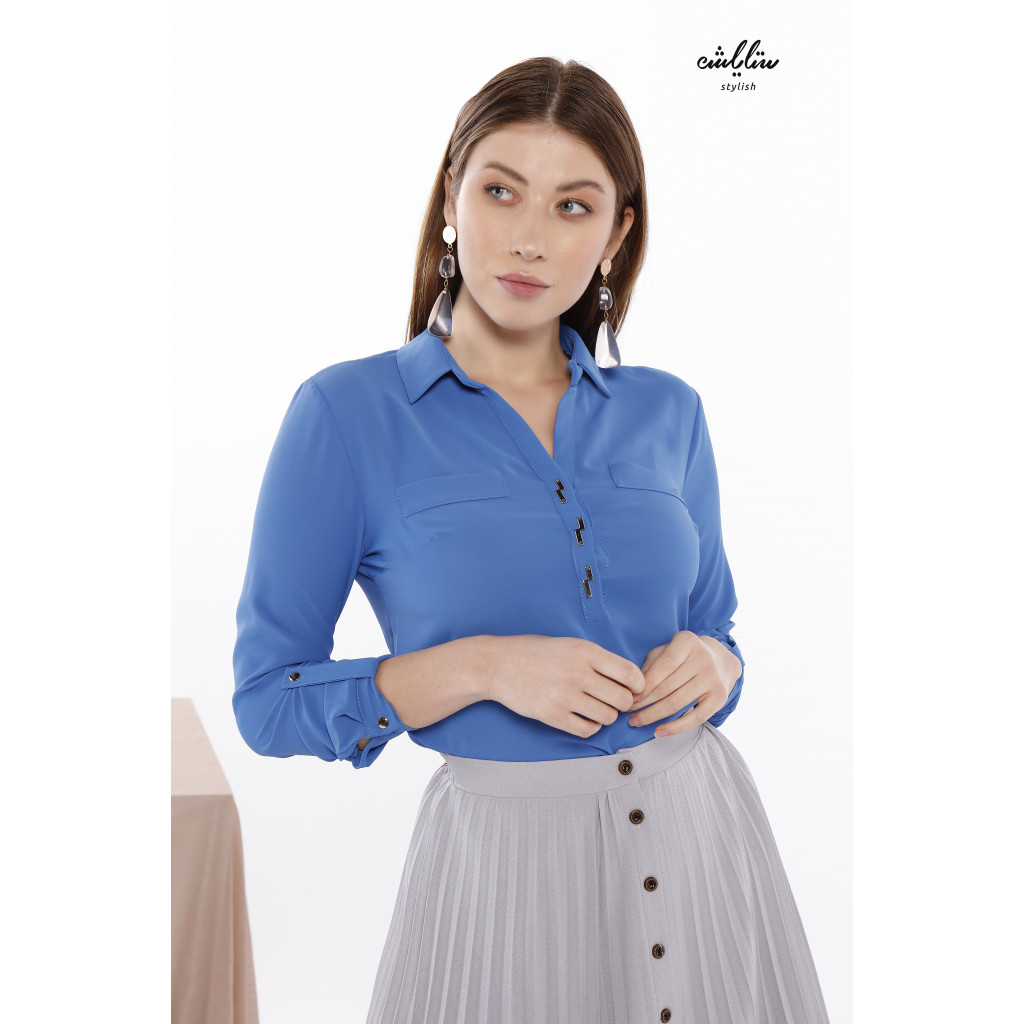 An elegant blouse in blue with a formal collar decorated with buttons.