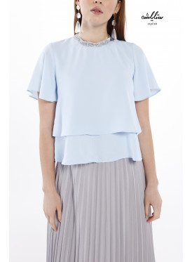 An elegant baby blue blouse with short sleeves, layers