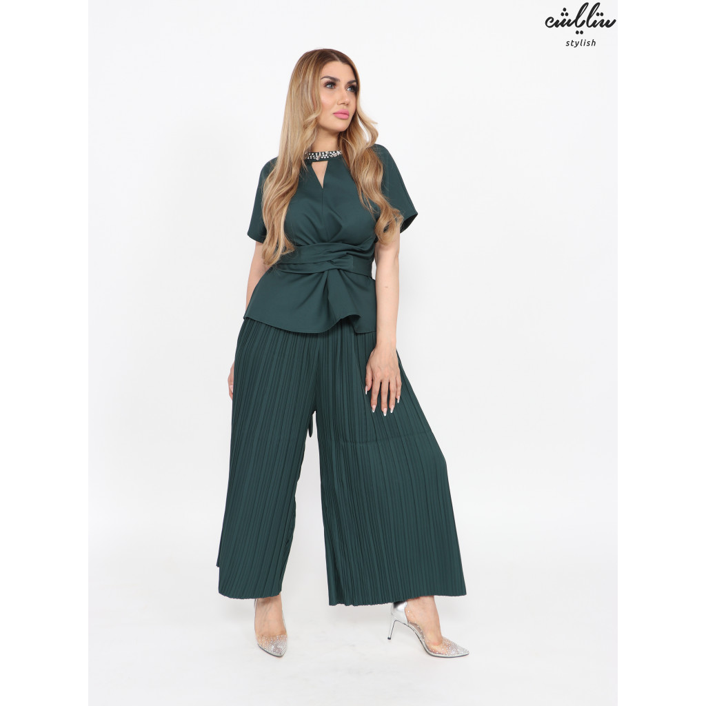 An elegant set of green pleated pants and crystals on the neck