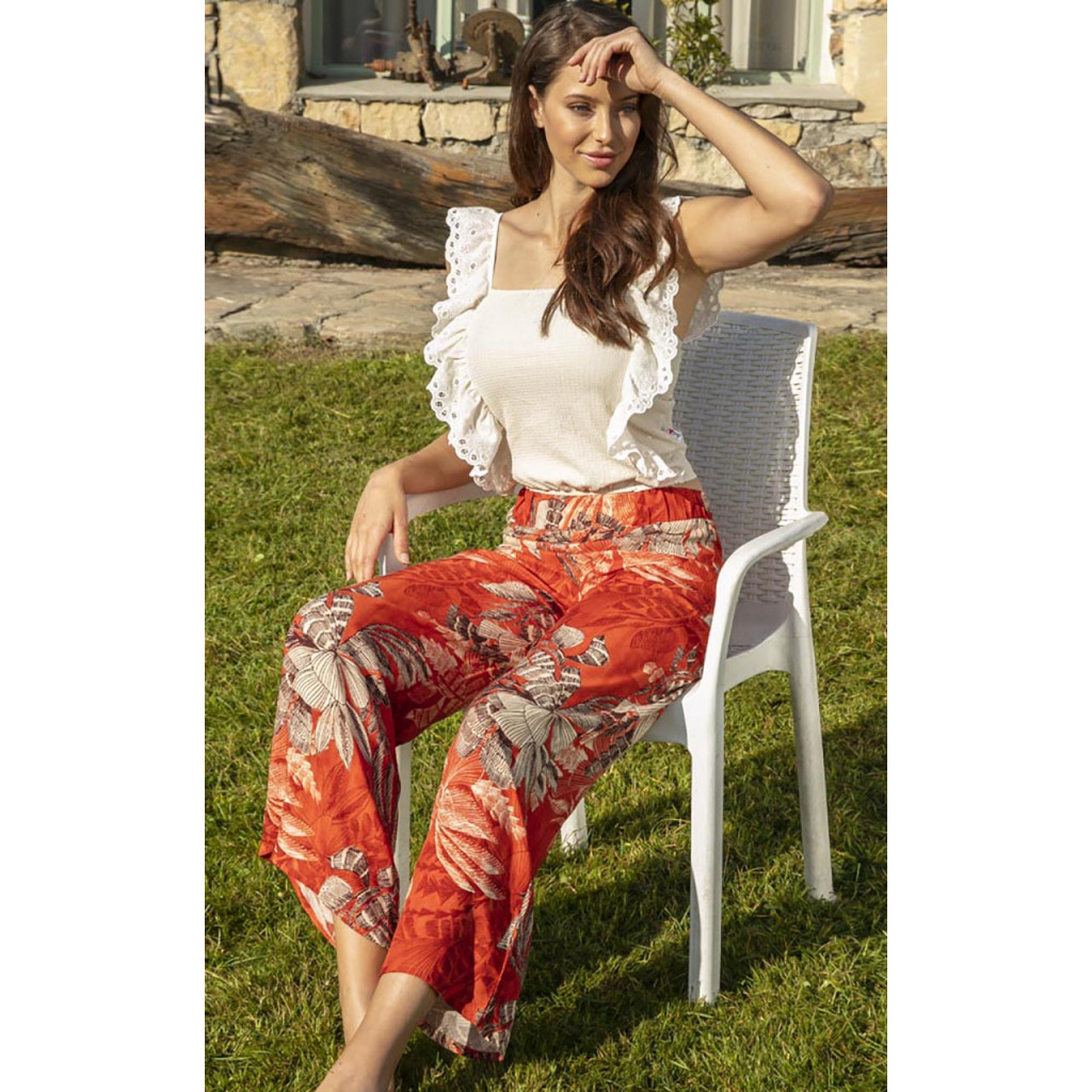 Stylish home dress consisting of white bare shoulder blouse decorated with side pleats and red wooded trousers for a feminine look.