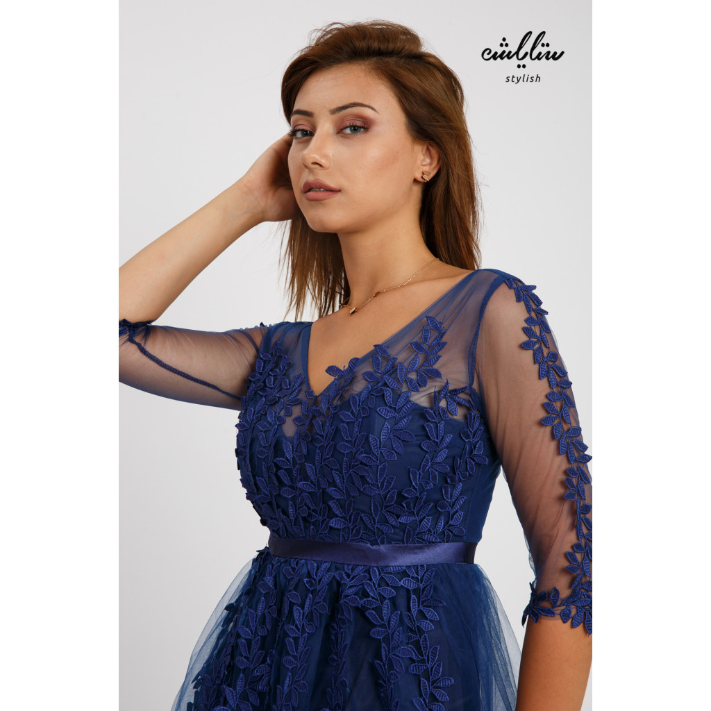 A long, elegant blue dress with a wide cut and softness that accentuates the beauty of the rose-adorned chiffon