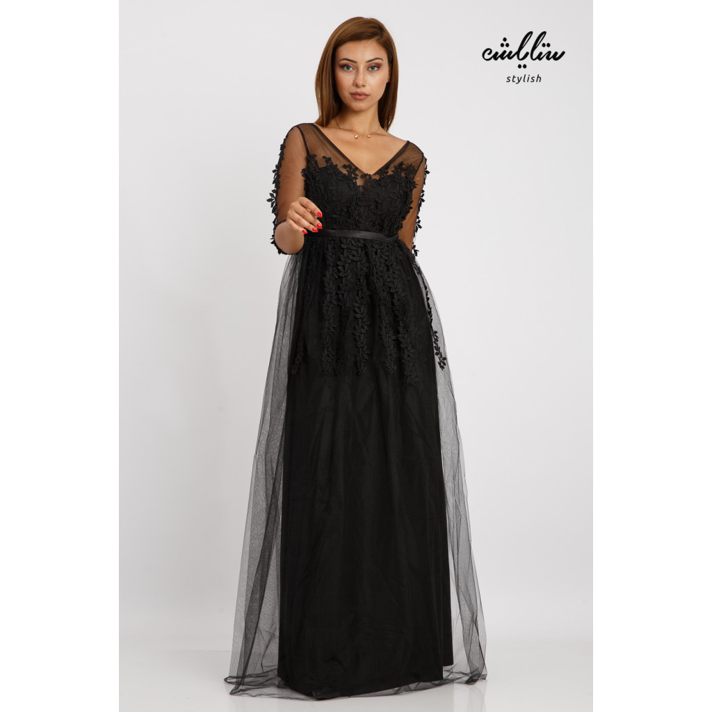A long, elegant black dress with a wide cut and softness that accentuates the beauty of the rose-adorned chiffon
