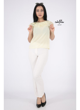 Blouse in yellow light with you from the top decorated with lace strap and pearl beads