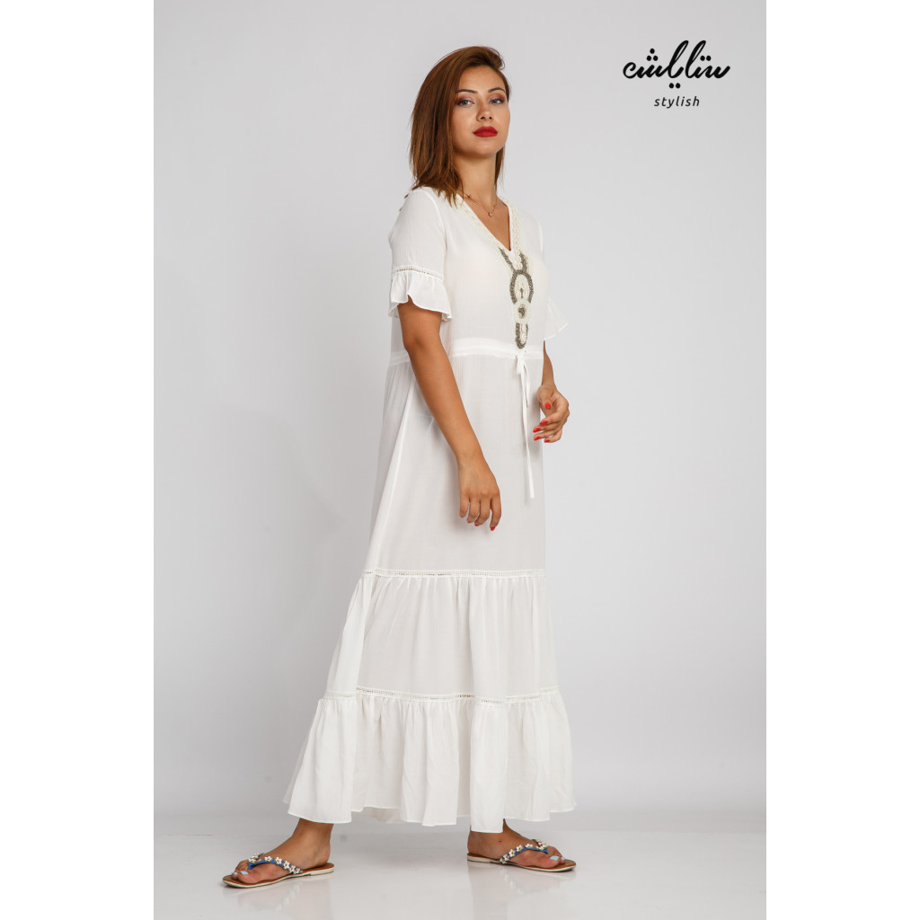 White maxi dress decorated with soft plungs and a strap on the waist, practical and comfortable